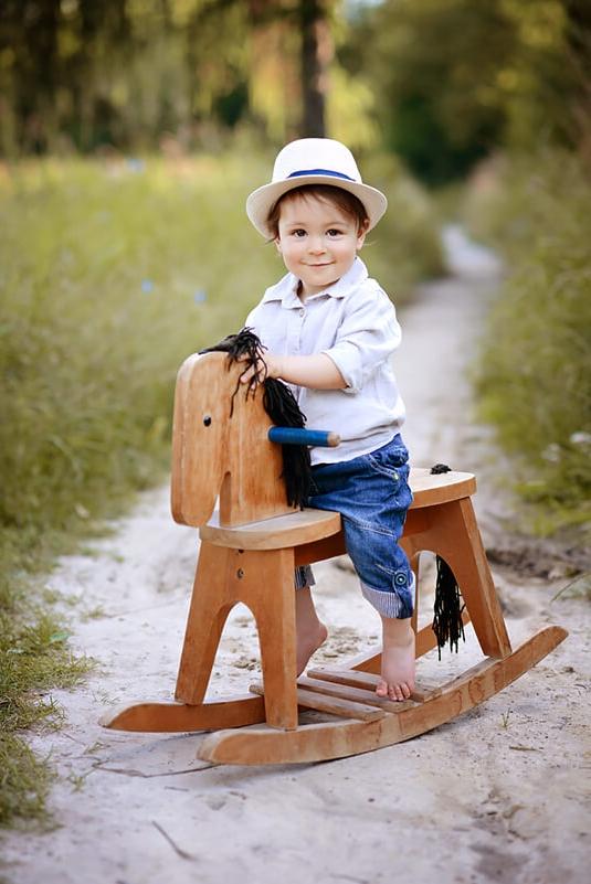 sesja dziecięca w plenerze chlopiec na drewnianym koniku