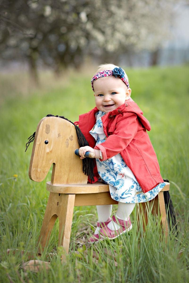 Zdjęcie dziecka na drewnianym koniku w plenerowej sesji rodzinnej