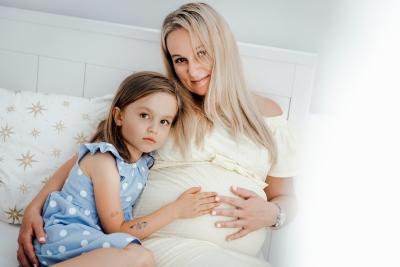Mama w ciąży pozuje do zdjęć z córką
