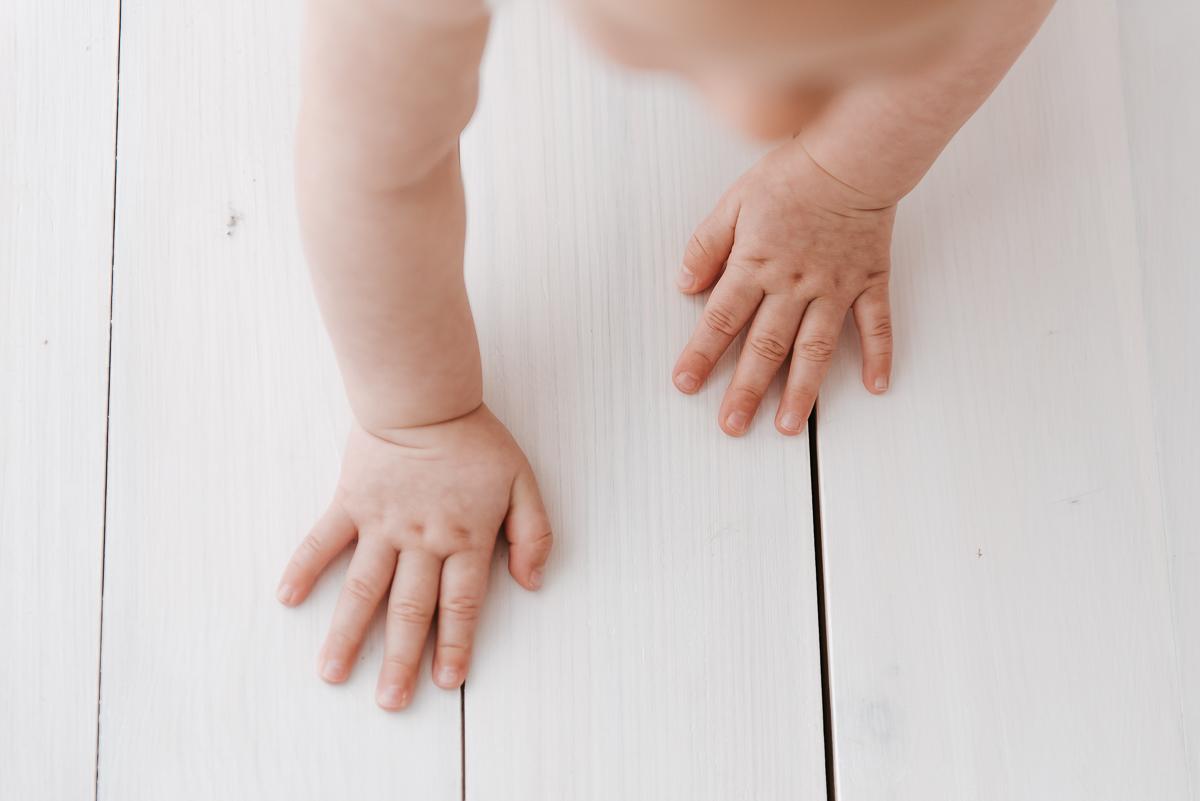 Dłonie w zbliżeniu na sesji fotograficznej niemowlaka