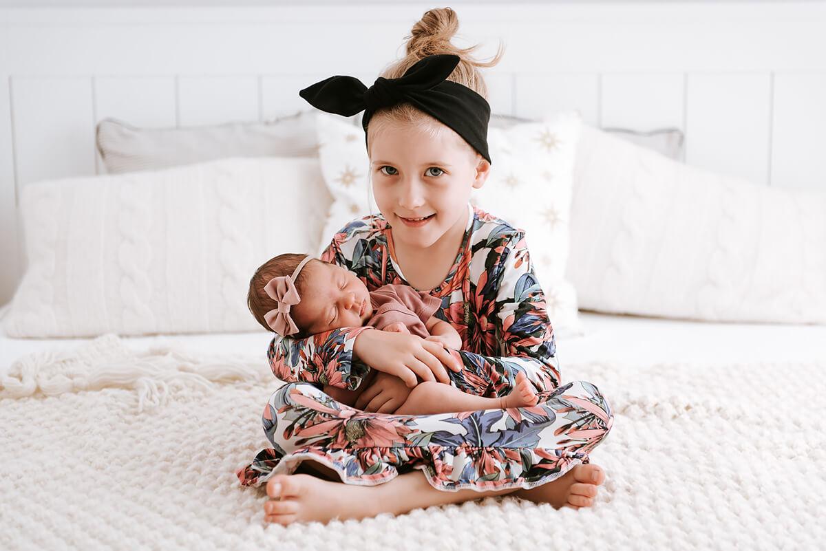 Sesja fotograficzna noworodka na rękach u swojej siostry
