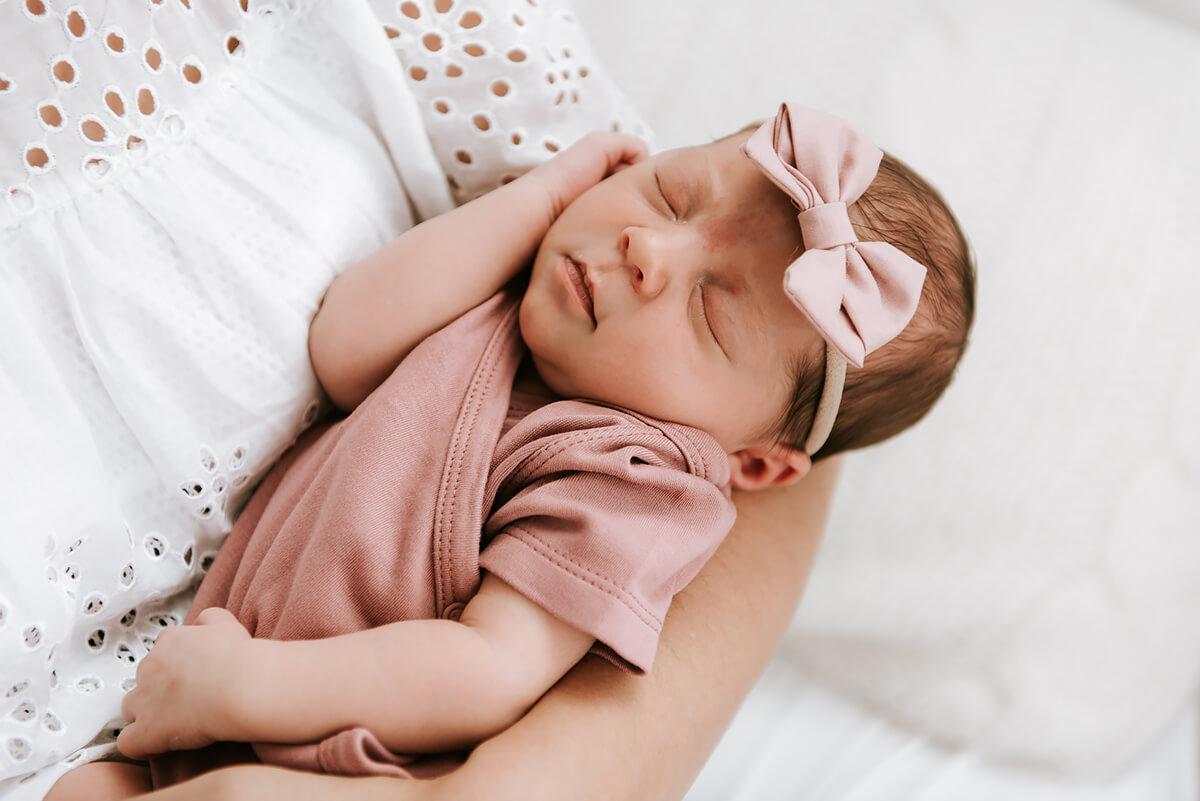 Noworodek na rękach u mamy sesja fotograficzna