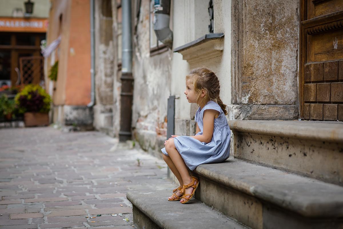 Sesja dziecięca przedstawia dziecko na schodach