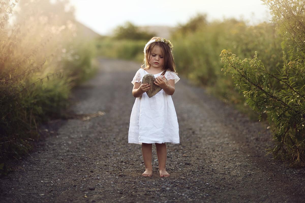 Zdjęcie dziecka na tle zachodzącego słońca