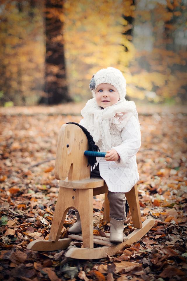 Plenerowa sesja dziecka na drewnianym koniku